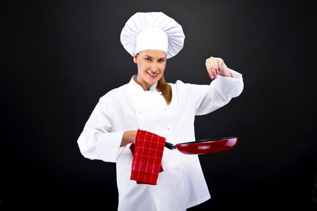 cheff woman over dark smiling and cooking Stock Photo