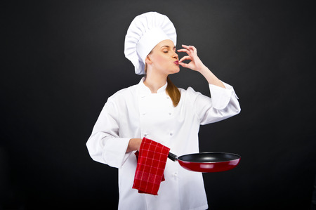 whites: Young female chef kissing her hand to show perfection over dark background. Vertical shot.   Stock Photo