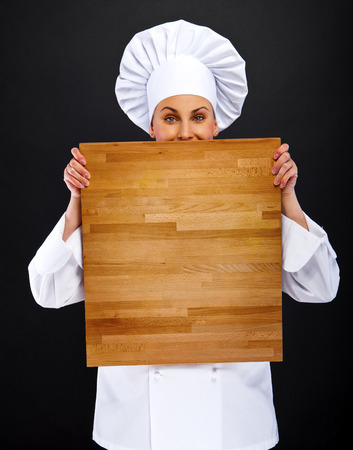 woman chef holding wooden board pionting with smile photo
