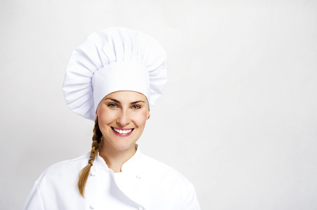 A young, female chef in a traditional hat and coat. Stock Photo