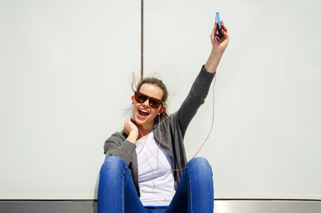 very windy: beautiful young brunette hair hipster woman listening music earphones in the city