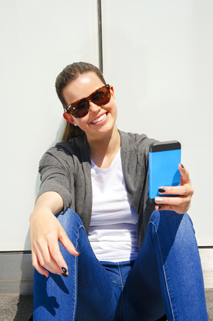 Pretty young woman using mobile phone photo