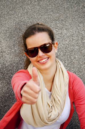 Gorgeous young brunette showing big thumbs up on urban location. photo