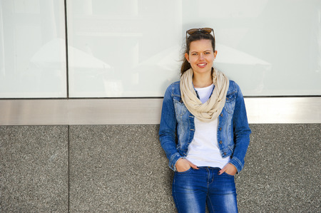 girls in jeans: Beautiful urban woman, girl standing by the wall in city wering jeans jacket Stock Photo
