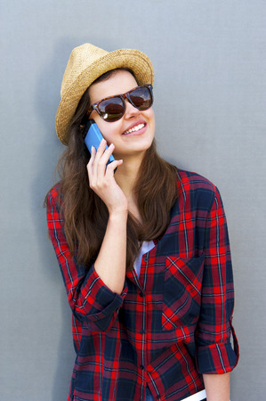 Young happy teen girl using a smart phone, tablet over wall in the background and big smile