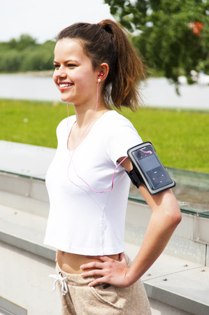 listing: Jogging girl in the city listing music by headphones