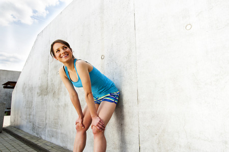 rest: young woman resting after run by the wall in city with big smile. in blue sportswear.