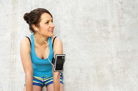 listing: young woman resting after run by the wall in city with big smile. in blue sportswear. listing music. Stock Photo