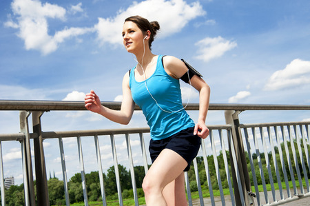 brige: Young woman runing in the city over the brige in sun light, smiling.