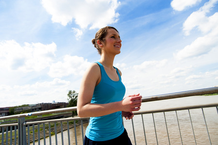 brige: Young woman runing in the city over the brige in sun light.