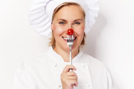 nariz roja: Mujer del cocinero holdinh un tenedor con tomate contra la nariz, de pie contra el fondo blanco sonriente.