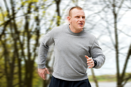 jogger: Man run by the river. Outdoor jogger. Blured background. Stock Photo