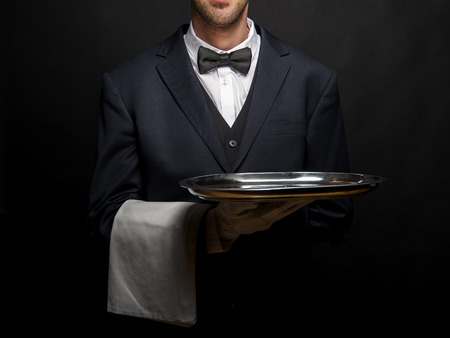 Waiter in black suit holding tray over black background.