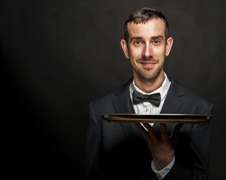 Camarero en la bandeja del traje de retención negro sobre fondo negro. Foto de archivo