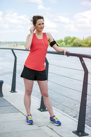 jogger: Fit woman jogger resting after run listening music. Stock Photo
