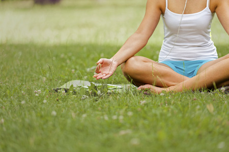 lotos: Relax woman in lotos pose on grass. Stock Photo