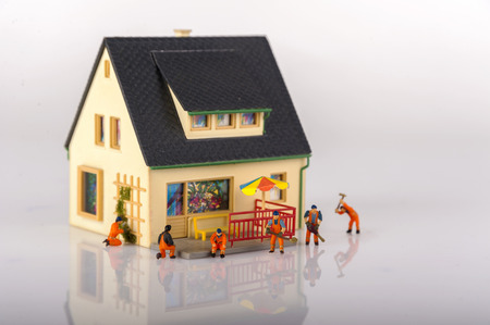 Miniature people workers and house