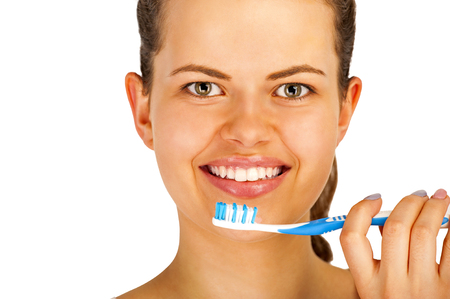 bathroom mirror: Young woman brushing teeth over white backgrund.
