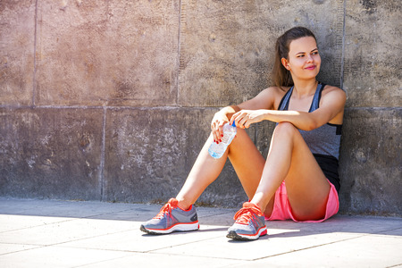 Young smiling female resting after an active training with water bottle while siting on sidewalk, satisfied fit woman resting after an active training, drinking cold water. Stock Photo