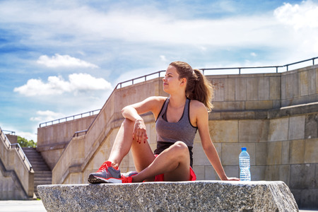 staying fit: Young smiling female resting after an active training with water bottle while siting on rock, satisfied fit woman resting after an active training.