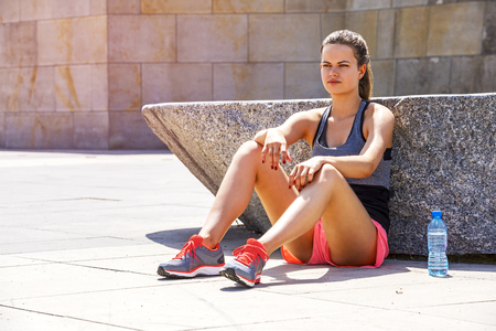 staying fit: Young smiling female resting after an active training with water bottle while siting, satisfied fit woman resting after an active training. Stock Photo
