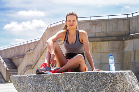 staying fit: Young smiling female resting after an active training with watter bottle while siting on rock with copy space area for your text message, satisfied fit woman resting after an active training Stock Photo
