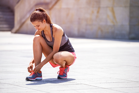 Running shoes - woman tying shoe laces. Female sport fitness runner getting ready for jogging outdoors in city by summer in full sun. Stock Photo