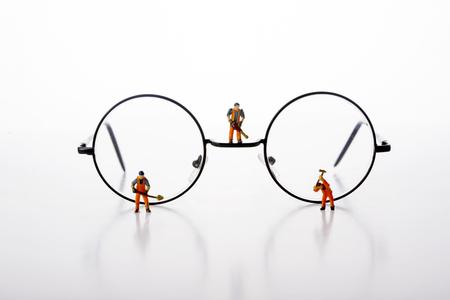 De miniatuurmensenarbeiders lopen door glazen over witte achtergrond.