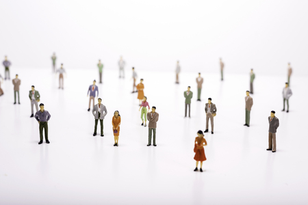Group of miniature people over white background.
