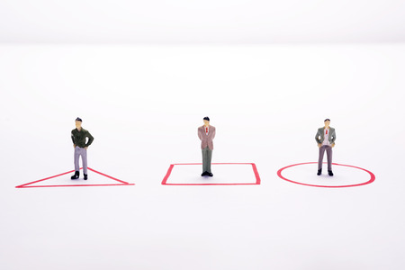 Miniature people three business men standing in red diagrams over white background or backdrop.