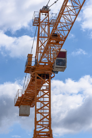 slew: A yellow construction cranes above a cloudy sky.