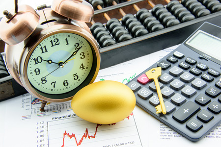 money time: Golden egg and a golden key with a clock on business and financial reports : Key success in sustainable growth investment concept