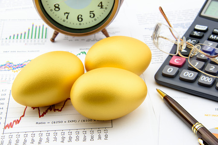 Drie gouden eieren met een klok, oogbril, een calculator en een pen op zaken en financiële samenvattingsrapporten. Een langetermijn duurzaam groei beleggingsconcept.