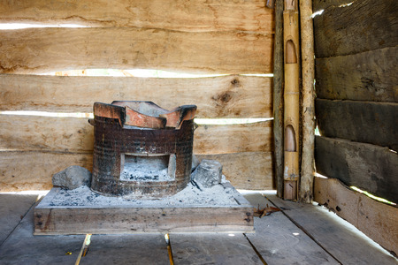 burning house: Traditional charcoal burning clay stove in a rustic wooden house.