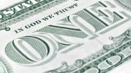 ism: The United States one dollar bill, a macro closeup emphasizing the inscription In God We Trust printed on the back.