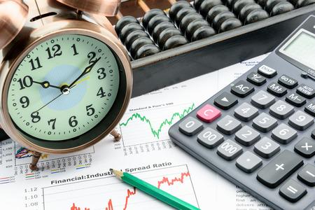 Een klok met een rekenmachine, een telraam en een potlood op het zakelijke en financiële samenvattende rapporten. Een lange termijn duurzame groei van de investeringen concept.