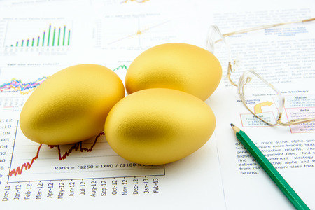 financial reports: Three golden eggs with a pencil and eye glasses over business and financial summary reports. Key success in sustainable growth investment concept.
