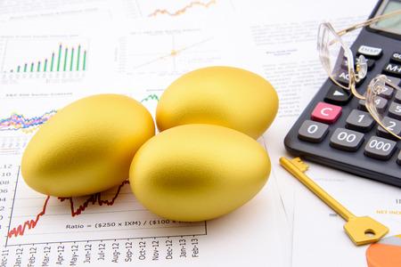 ingresos: Tres huevos de oro y una llave de oro con una calculadora en informes comerciales y financieros: clave de éxito en el concepto de inversión el crecimiento sostenible