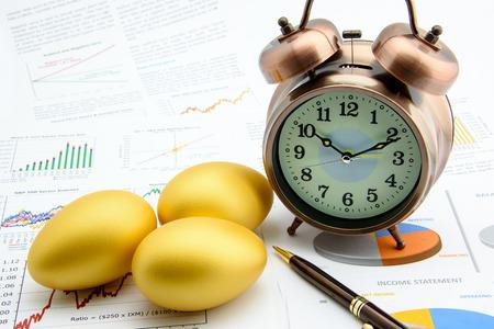 Drie gouden eieren met een klok op zakelijke en financiële verslagen: Investeringen Concept Stockfoto