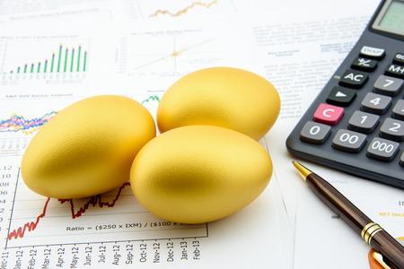 Tres huevos de oro con una calculadora en informes comerciales y financieros: Concepto de la inversión