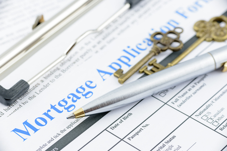 mortgage application: Blue ballpoint pen and two vintage brass keys on a mortgage application form, preparation for filling a form on a clipboard.