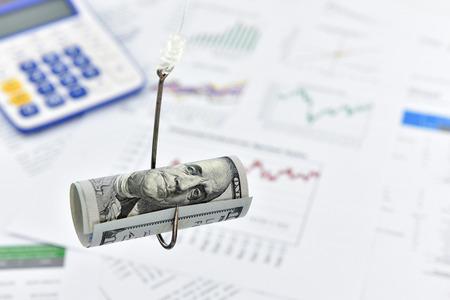 esquema: Enrollada desplazamiento de US billete de 100 dólares en un anzuelo. Un concepto de engañar a alguien en varios campos  mercado  comerciales, es decir financiera, moneda, divisas, valores, acciones, bonos, derivados, acciones, etc.