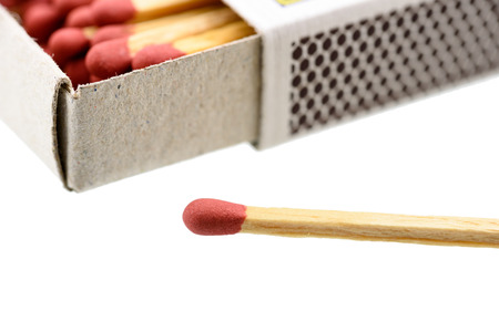 ignited: Matchbox, a small paperboard box enclosing a quantity of matches in the interior tray and having a coarse striking surface on the exterior. With a matchstick outside box isolated on white background.