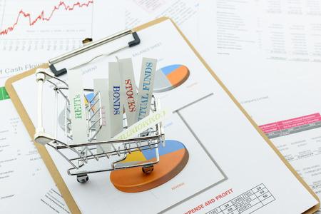 Diverse types financiële en beleggingsproducten in een winkelwagentje ie REIT's, ETF's, obligaties, aandelen. Duurzaam portfolio, op lange termijn vermogensbeheer met risicospreiding concept.