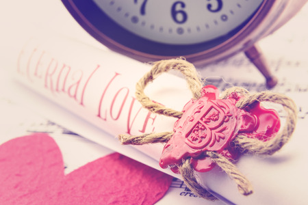 sealing wax: Rolled up scroll of love poem fastened with natural brown jute twine hemp rope, sealed with sealing wax and stamped with alphabet letter B. Decorated with a red mulberry paper heart and vintage clock. Stock Photo