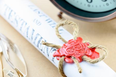 Enrollada desplazamiento del testamento atado con cuerda de yute hilo de cáñamo marrón natural, sellado con lacre y estampado con la letra del alfabeto B. decorado con un reloj antiguo y gafas.