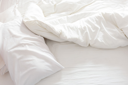 Top view of an unmade bed with crumpled bed sheet, a blanket and pillows after waking up in the morning.