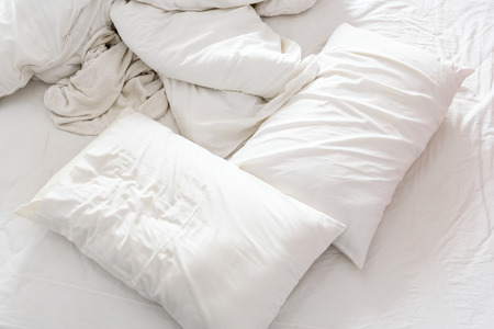 bedclothes: Top view of an unmade bed in a bedroom with crumpled bed sheet, a blanket, a white shower towel and two pillows after waking up in the morning. Not having bedclothes neatly arranged for sleep in.