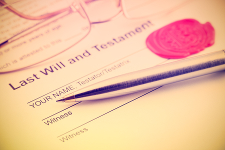 Vintage / retro style : Last will and testament sealed with wax seal, stamped / embossed with alphabet letter B. With a blue ballpoint pen and eye glasses on a table. Stockfoto