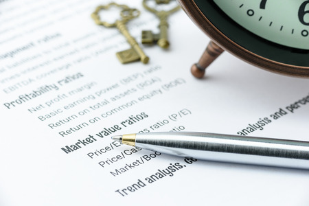 Blue ballpoint pen on a financial ratios analysis check lists with an antique clock and two vintage brass keys. Financial, business and investment analysis concept. Stock Photo